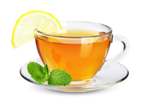 Cup of tea with slice of fresh lemon and mint isolated on white